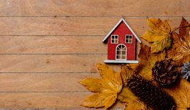 Little vintage house with maple leaves. On wooden table. Above view stock image