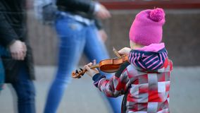 The little violinist was playing on the street stock footage