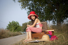 Little voyager. Sweet little girl with old suitcases on the road , ready to travel to the big world royalty free stock photo