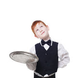 Little waiter thoughtful, dreaming with empty tray. Smiling inattentive redhead child boy in suit play restaurant servant at blue background Royalty Free Stock Image