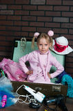 Little warmly dressed girl packs a suitcase with summer things Royalty Free Stock Image