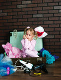 Little warmly dressed girl packs a suitcase with summer things Stock Images