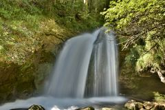 Waterfall over a grotto in a shiny green forest royalty free stock photos