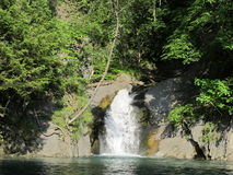 Little waterfall flows into the Blue Lake, Grenoble Stock Photography