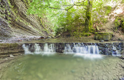 Little waterfall in mountain forest with silky foaming water royalty free stock photo
