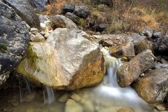 Little waterfall with rannig water in rocks. Soft Little waterfall with rannig water in rocks on autumn Stock Images