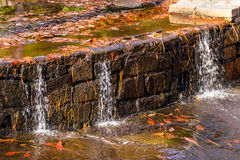 Little waterfall with stonework on creek. Little waterfall with the stonework on the creek with dry leaves in sunny autumn day Stock Images