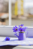 Little watering can with spring flowers bouquet near the window Royalty Free Stock Image