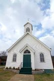 Little Wedding Chapel. Closeup of small white church with green door from low viewpoint, slight distortion Stock Photo