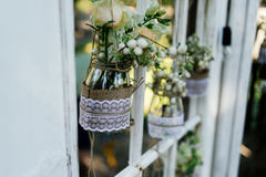 Little wedding floral decorations in rustic style hang in jars. Decorated with sacking and lace Royalty Free Stock Photography
