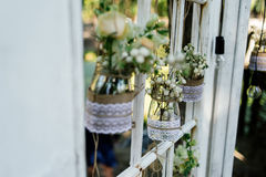 Little wedding floral decorations in rustic style. Hang in jars decorated with sacking and lace Stock Photo
