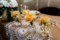 Little wedding floral decorations. Of yellow roses are in vases on dinner table Stock Image