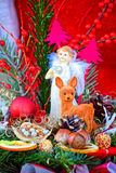 Little white angel with wings and a fawn. Little white angel with wings and a fawn standing next to a green fir tree branches, nuts, chocolates with red ribbons Royalty Free Stock Photography