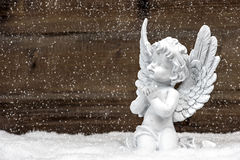 Little white angel on wooden background in snow. Little white guardian angel in snow on wooden background. vintage style christmas decoration with falling Stock Photo