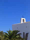 Little white church in Ibiza. Typical little white church in Ibiza (Spain), with blue sky and palms Royalty Free Stock Photography