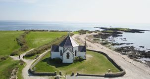 Little white church next to the ocean, aerial view stock footage