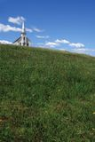 Little white church over the hill. Photo of a little white wooden church on the top of a hill Royalty Free Stock Image