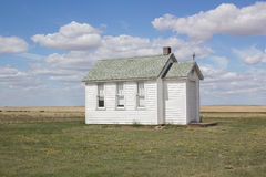 Little white church on the prairies. Little white church on a prairie landscape with blue skies and clouds Royalty Free Stock Images