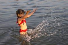 Little white girl children make water splashes Stock Photos