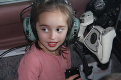 Little white girl sitting in airplane with headphones Royalty Free Stock Image