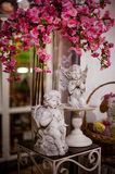 Little white guardian angels with pink flowers. Little white guardian angels with a pink flowers Stock Photography