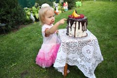 A little white-haired girl of two years is trying a birthday cake. Little girl celebrating second birthday. Stock Image