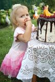A little white-haired girl of two years is trying a birthday cake. Little girl celebrating second birthday. Royalty Free Stock Images