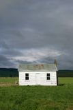 Little white house. With corrugated iron roof and chimney surrounded by fields and forested hills Stock Image
