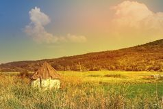 Little white old rural house surrounded by a sunny landscape, summer fresh day, hill covered with green grass and huge clouds. Little white old rural house Royalty Free Stock Image