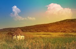 Little white old rural house surrounded by a sunny landscape, summer fresh vital day. Hill covered with green grass and huge clouds floating in the sky Royalty Free Stock Photos
