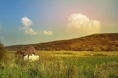 Little white old rural house surrounded by a sunny landscape, summer fresh vital day. Hill covered with green grass and huge clouds floating in the sky Stock Photos