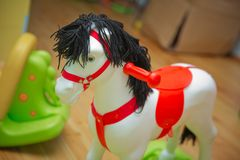 Little white pony rocker swing doll on a wooden floor . Swing horse with leather belt on a wooden floor next to a stock image
