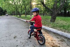 A little white Toddler boy wearing a protective helmet on his he. Ad rides a bicycle. Toddler on a two-wheeled red bicycle Stock Images