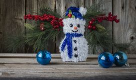 Little white toy snow man with blue scarf and hat on wood background. Stock Images