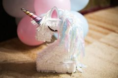Little white unicorn made of paper with a mane, against the background of balloons stock photo
