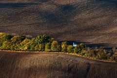 Little white wedding chapel hidden behind the trees in the autumn, amid the plowed fields.Kyjov South Moravia.Czech Republic. Royalty Free Stock Image