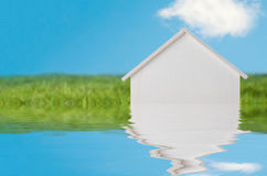 LIttle White Wooden House Sinking into Water. Conceptual photograph of a white wooden house in bright green grassy landscape with blue sky, appearing to sink royalty free stock images