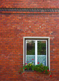 Little window. Window with flowers on brick wall Stock Photo