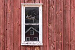 A little window in front of a typival scandinavian building with falu red. Was seen in Sweden stock image