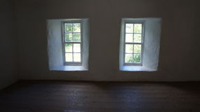 Little Windows. A shot of two small windows with light shining in onto the floor boards in an old country house Stock Image