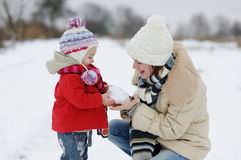 Little winter baby girl and her young mother Stock Images