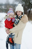 Little winter baby girl and her young mother royalty free stock photo