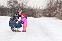 Little winter baby girl and her young mother Stock Photos