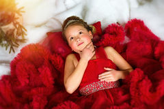 Little winter Princess lies on artificial New year snow Stock Photos