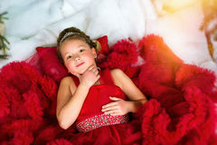 Little winter Princess lies on artificial New year snow Stock Images