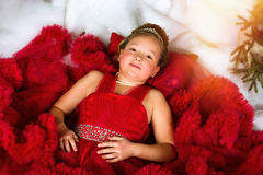 Little winter Princess lies on artificial New year snow Royalty Free Stock Images