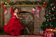 Little winter Princess warms at burning fireplace. Little winter Princess, girl in red dress, warms his hands at the burning fireplace. Celebration of New year Royalty Free Stock Photos