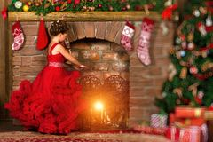 Little winter Princess warms at burning fireplace. Little winter Princess, girl in red dress, warms his hands at the burning fireplace. Celebration of New year Stock Images