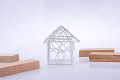 Little wired metal model house  and domino pieces Royalty Free Stock Photos