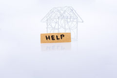 Little wired metal model house and the word HELP Stock Photo